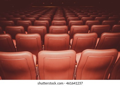 Movie theatre seats in red colors in a dark room