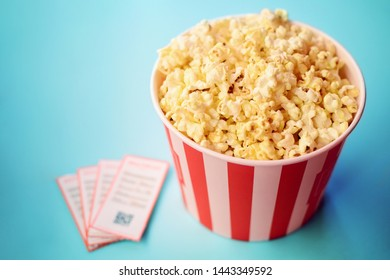 Movie tickets, big striped box of popcorn on blue table before watching movie in cinema