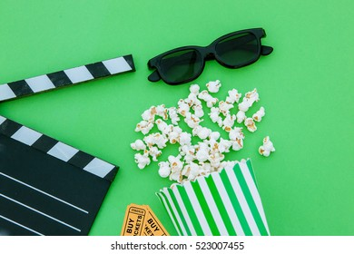 movie tickets, clapperboard, pop corn and 3d glasses in a green background.Flatlay