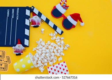 movie tickets, clapperboard, pop corn and 3d glasses in a yellow background..Flat lay .Christmas concept