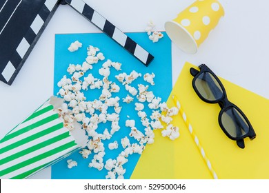 movie tickets, clapperboard, pop corn and 3d glasses in a white, blue and yellow background.Flatlay
