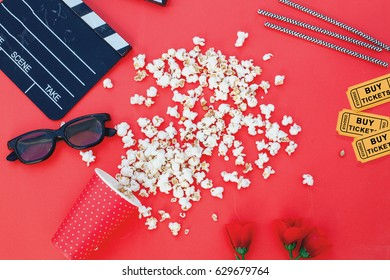 movie tickets, clapperboard, pop corn and 3d glasses in a red frame background..Flat lay