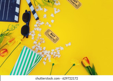 movie tickets, clapperboard, pop corn and 3d glasses  flowers in yellow background.Spring.  concept.Flat lay.