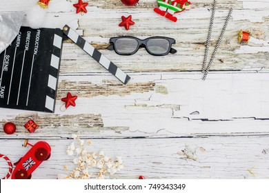 movie tickets, clapperboard, pop corn and 3d glasses in a rustic white wooden table background..Flat lay .Christmas concept