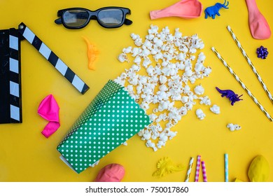 movie tickets, clapperboard, pop corn and 3d glasses in a yelow  background .Flat lay.Birthday party concept