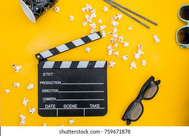 movie tickets, clapperboard, pop corn and 3d glasses in yellow background..Flat lay .party concept
