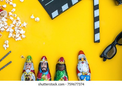 movie tickets, clapperboard, pop corn and 3d glasses in a yellow background..Flat lay . three wises men  concept