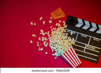 Movie tickets, clapperboard, pop corn on red background