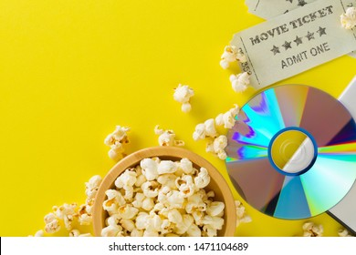 Movie tickets, DVD or blu ray disc and popcorn on yellow table background. Home theatre movie or series night concept. Flat lay top view from above with copy space.