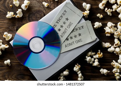 Movie tickets, DVD or blu ray disc and popcorn on dark wooden table background. Home theatre movie or series night concept. Flat lay top view from above.