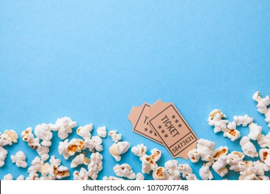 Movie tickets and popcorn on blue background. Copy space for text