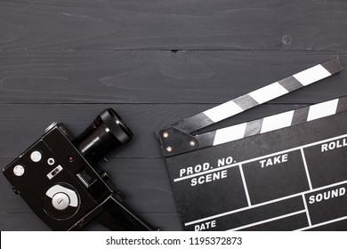 Movie time, flat lay with space for text. Cinema minimal concept. Cinema Clapperboard, retro camera on a black wooden background.