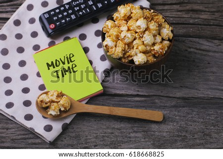 Movie Time word with popcorn and remote on wooden background