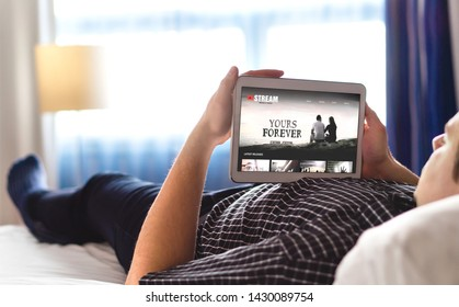Movie, video and online streaming service in tablet. Man choosing and watching digital film with smart device. Person relaxing. Tv network internet site on screen. On demand video (VOD) concept.