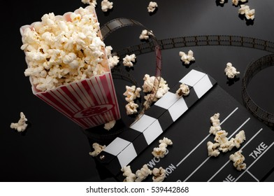 movies and entertainment concept with popcorn, film strip and clapper board