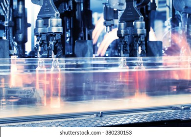 Moving assembly line for production of bottles toned in blue