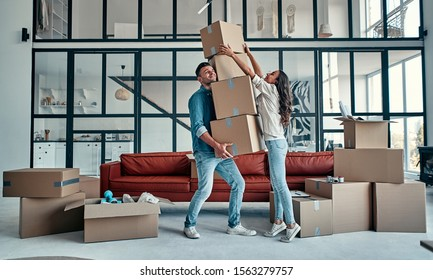 Moving, buying a house, apartment concept. Young couple with a bunch of falling boxes funny trying to catch them.