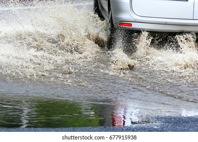 Moving car sprays puddle when heavy rain drops on concrete.