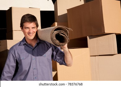 A moving an carrying a carpet with cardboard boxes in the background