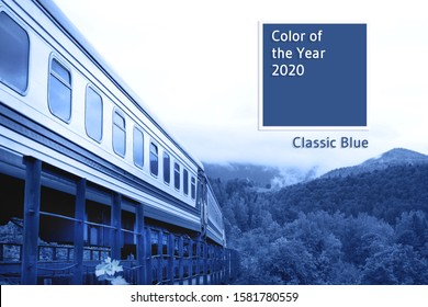 Moving classic train above the trees against the beautiful mountainous landscape toned blue. Main color trend of 2020 concept.