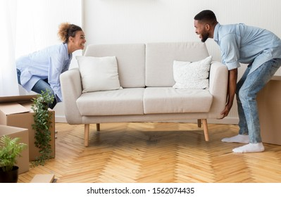 Moving Concept. Cheerful Afro Spouses Placing Couch Furnishing Empty Room In New House After Relocation