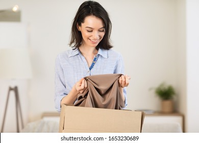 Moving Concept. Excited girl getting ready for moving out, packing clothes in paper box, copyspace