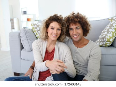 Moving couple sitting on the floor at home