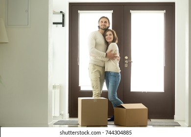 Moving day concept, excited young couple homeowners embracing in new home standing in modern hallway with cardboard boxes on floor looking around, mortgage loan, buying real estate and relocation