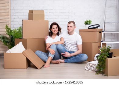 moving day concept - young couple resting after moving in new house or flat