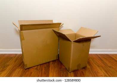 Moving day with empty cardboard boxes on hardwood floor.
