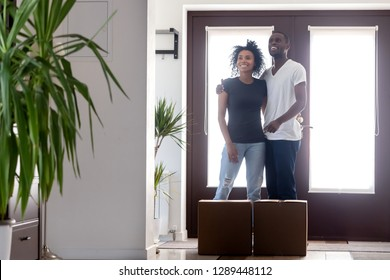 Moving day for millennial african couple concept, happy young black first time buyers home owners embracing standing in new modern luxury house hallway with boxes, family goals, mortgage, relocation