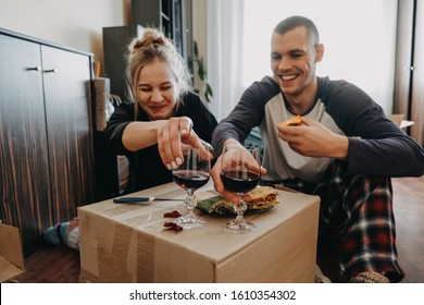 Moving Day, new home, Valentine's Day, unpacking boxes, newlyweds concept. Couple Celebrating Moving Into New Home With wine.