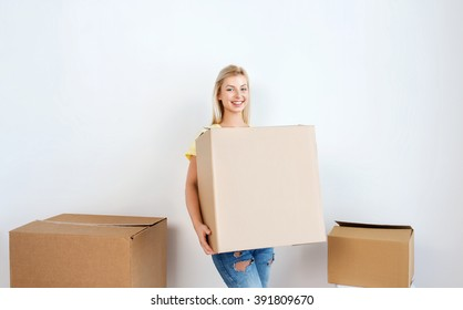 moving, delivery, housing, accommodation and people concept - smiling young woman with cardboard box at home
