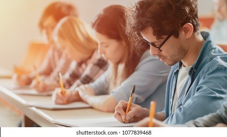Moving Footage of a Row of Multi Ethnic Students in the Classroom Taking Exam/ Test. Focus on Holding Pens and Writing in Notebooks. Bright Young People Study at University.