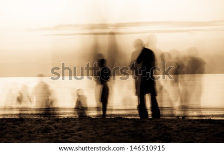 moving ghosts on the beach People walking on the beach at sunset. The movement blur makes it spooky. Duo tone