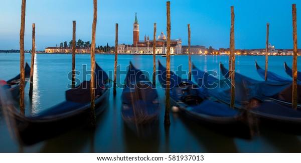 Moving Gondolas on Venice waterfront, San Giorgio Maggiore on the background