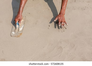 Moving hands and shadow of mason worker using steel trowel plastering aligns with cement floor, under construction concept.