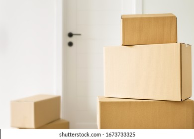 Moving home concept. Packed boxes with stuff in living room. Space for text