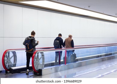 Moving horizontal walkway escalator (travelator/sidewalk) in international airport ternimal with walking people on it