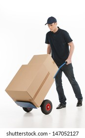 Moving house. Full length of young deliveryman with a hand truck transporting the cardboard boxes
