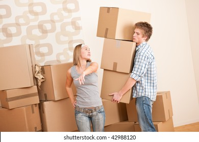 Moving house: Man and woman with box in new home
