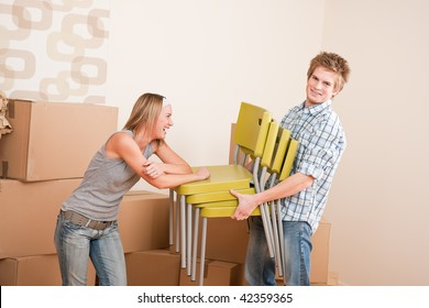 Moving house: Young couple with box and chair in new home