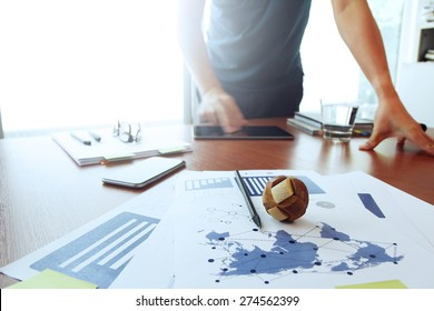 Moving Image of Business creative designer working wooden texture globe with smart phone on business document in office desk as internet concept