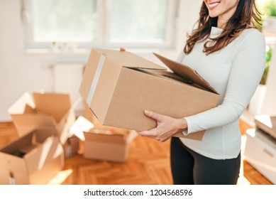 Moving in. Close-up image of female person carrying carton cardboard box.