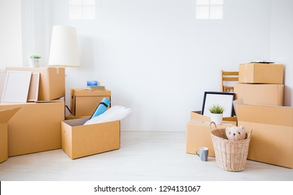 Moving in. Stack of cardboard boxes and household stuff belongings in the white empty apartment room with copy space. Lifestyle moving house relocation unpacking background concept