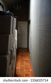 Moving in, stacks of cartons stored at narrow corridor in vintage style decorated apartment.