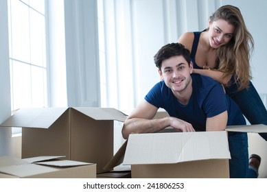 Moving new flat with fun and excitement. Young and beautiful couple is moving to new apartment surrounded with plenty of cardboard boxes. Both are smiling and having fun