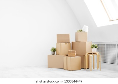 Moving to a new home. Belongings in cardboard boxes, books and green plants in pots stand on the gray floor against the background of a white wall. Concept relocation.