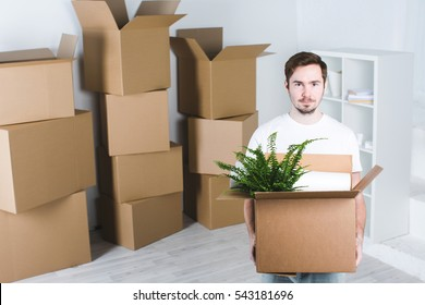 Moving in new house. Happy man with a box in his hands.