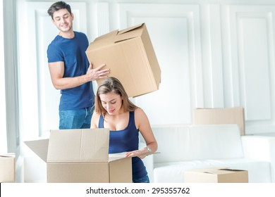 Moving to a new life. A girl and a guy holding boxes for moving the hands and smiling at the camera while a couple in love standing at the window among boxes